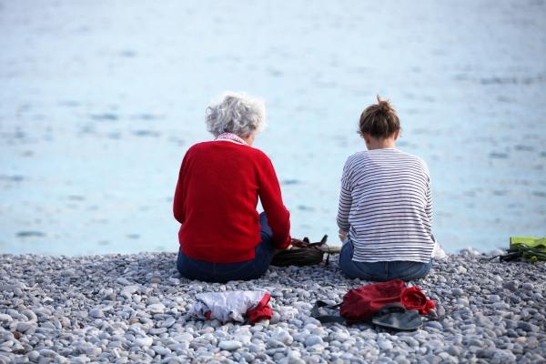 Alte und junge Frau sitzen am Strand, über dts Nachrichtenagentur